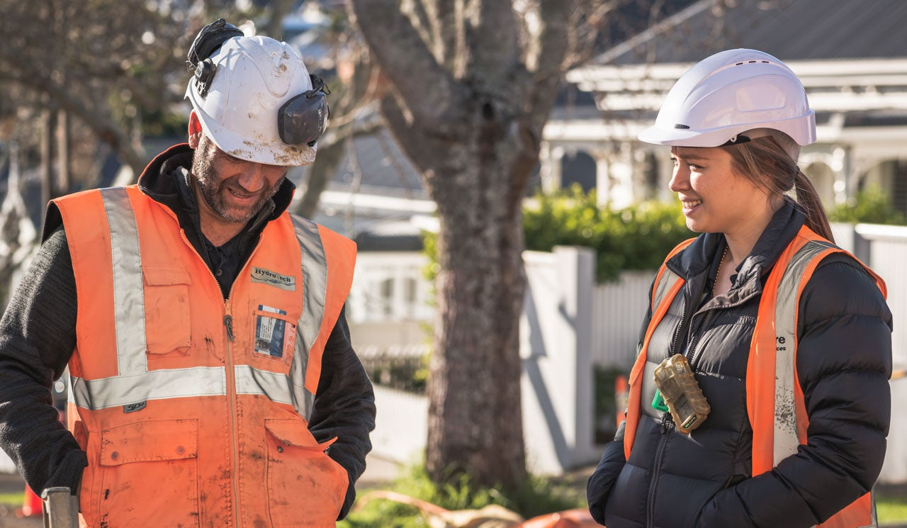 Sophie discusses an active pipework project with a contractor onsite in Ponsonby.