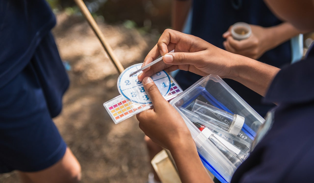 Northcross Intermediate School students test a water sample, using their Freshwater Detectives Kit colour reference charts and pH strips to measure the acidity of the water. Sample is taken from taken their local stream in Sherwood Reserve.