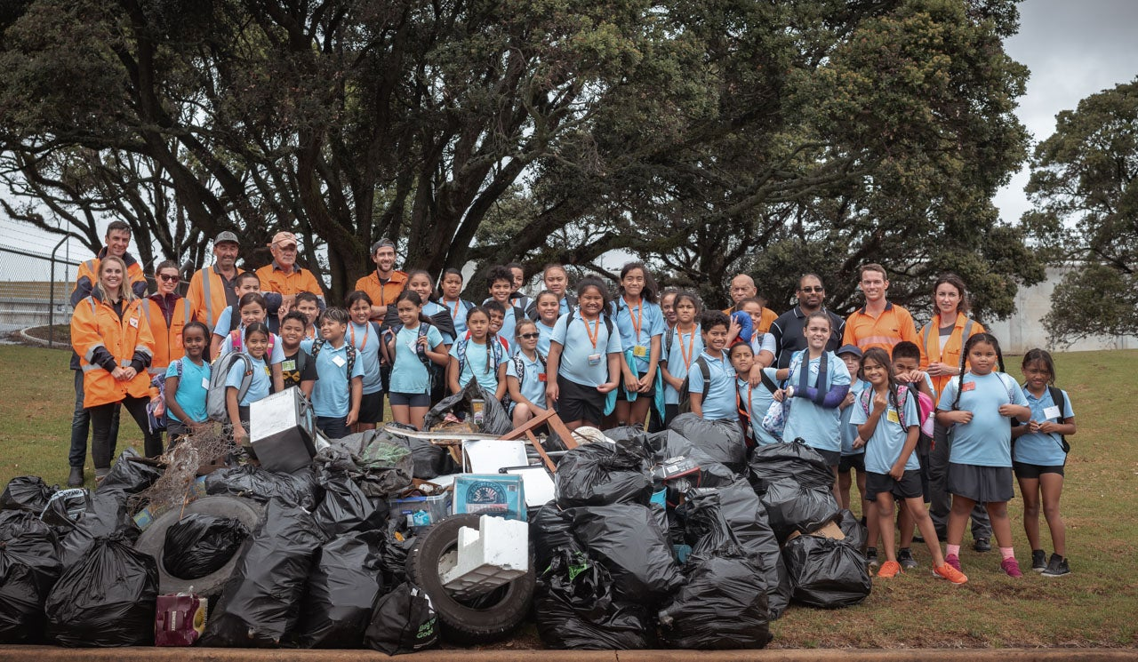 St Joseph's Grey Lynn School students, Watercare staff and volunteers stand proudly behind  their rubbish pile collected during the 2020 Sea Week beach clean up at and around the Māngere Wastewater Treatment Plant.