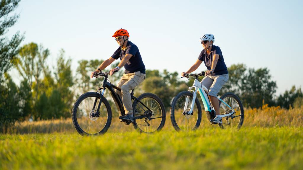 Seniors on two electric bikes, in a natural park setting.