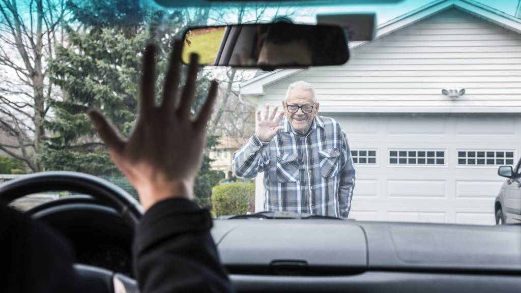 adult son waving to father from car