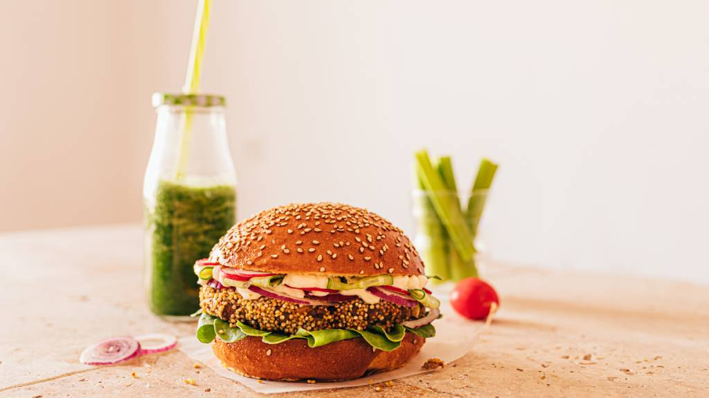 Vegan burger with asparagus spears and green smoothie