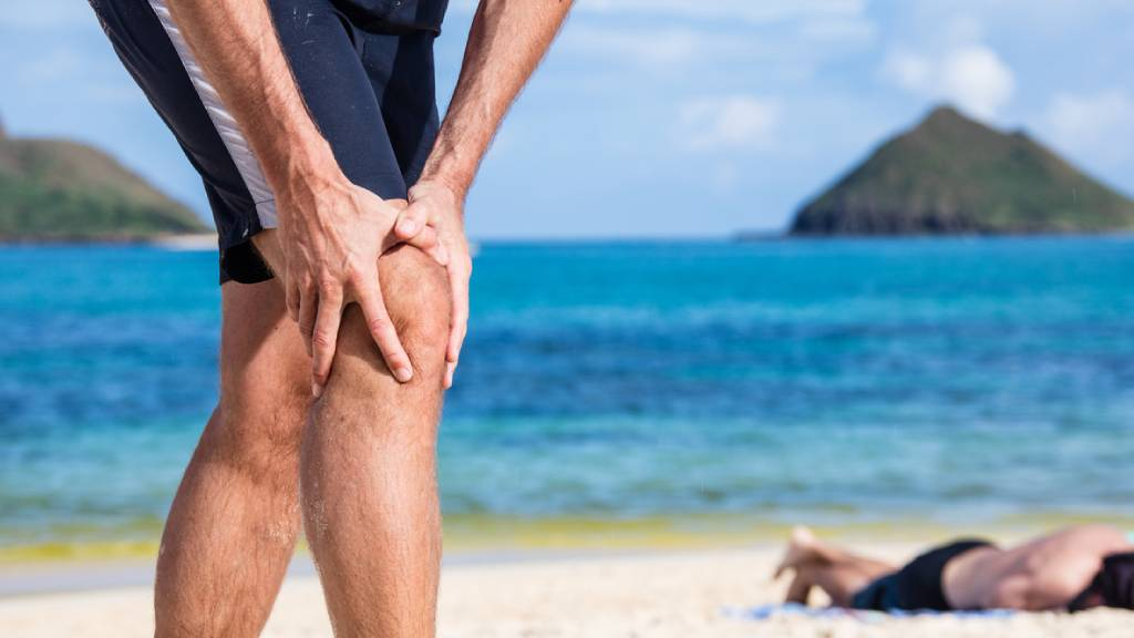 A senior suffering from knee pain in beach setting.