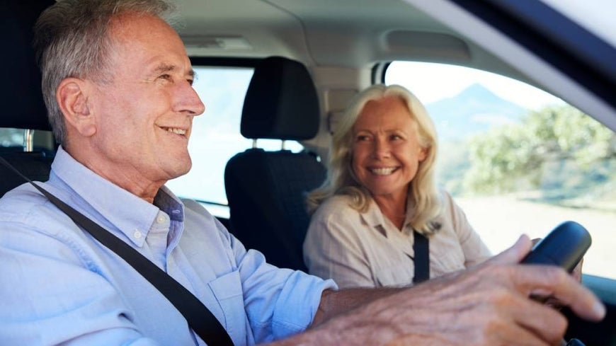 Senior couple drives in scenic location.