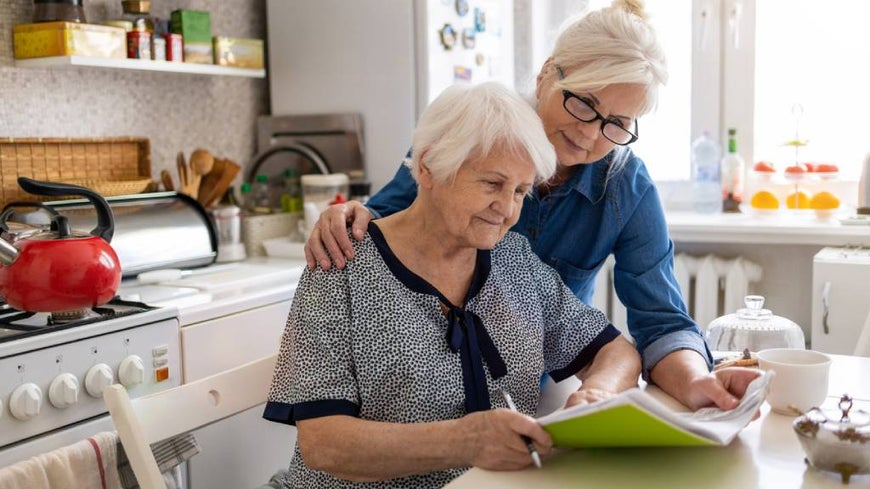 Woman is cared for by aged care worker in her home.