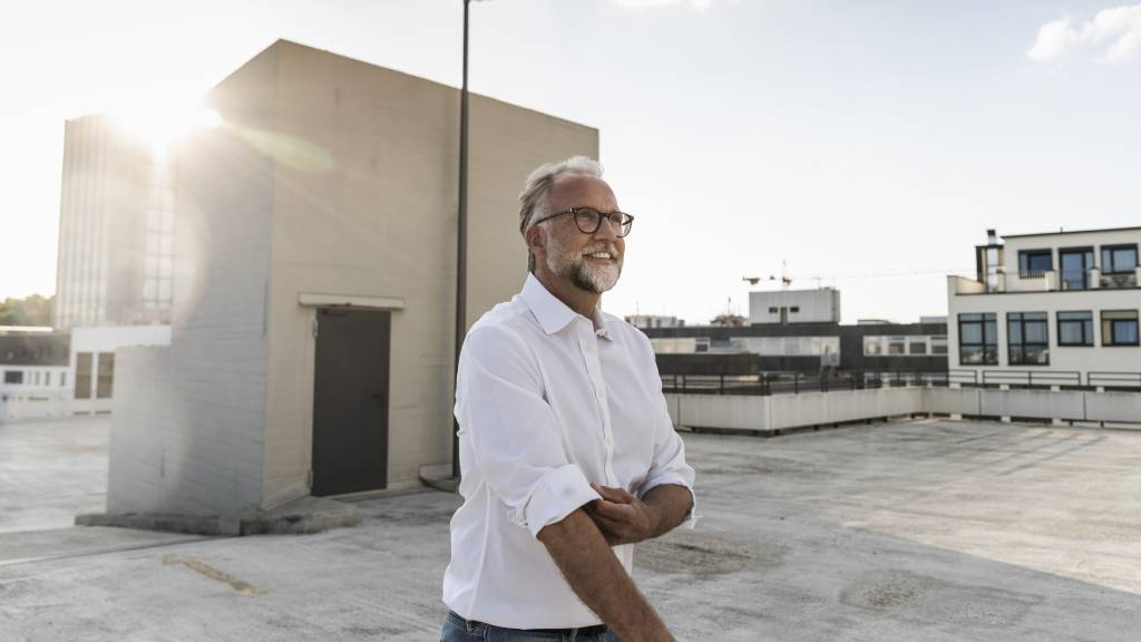 Man with white hair, beard and glasses rolling up his sleeves on a rooftop.