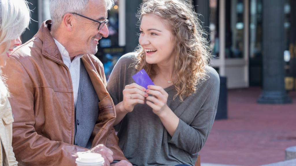 Young woman receives credit card from grandparents
