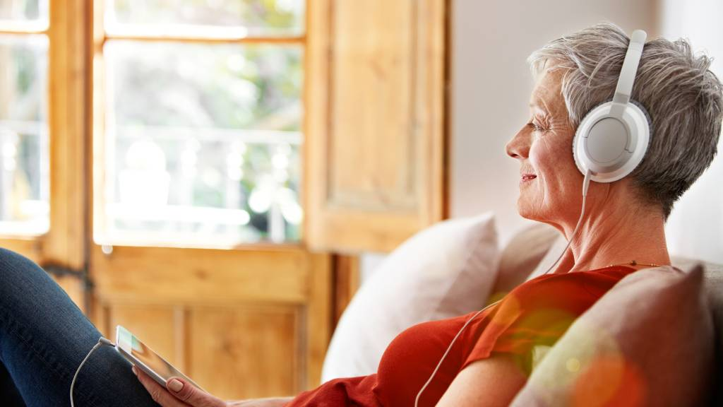 Older woman listens to music with headphones.