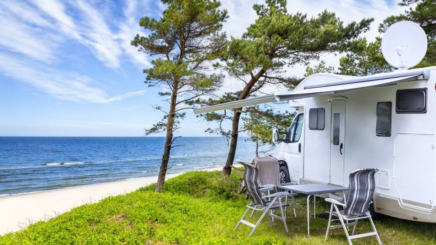 Caravan at a caravan park with table and chairs set out