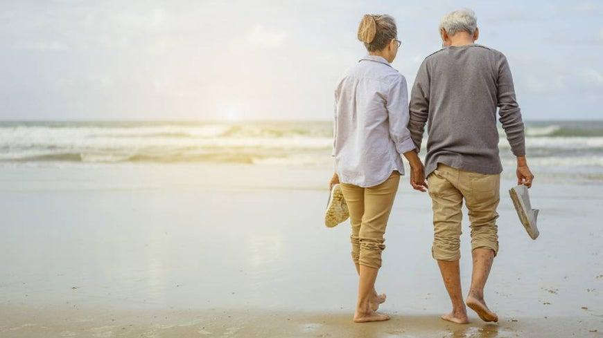 Senior couple watching sunset at the beach