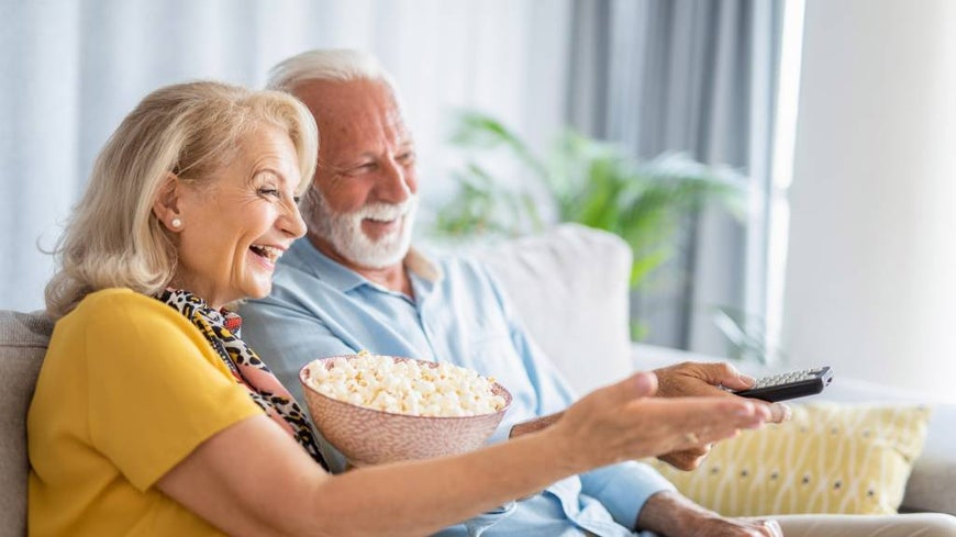 Happy senior couple watching a movie together in the lounge room