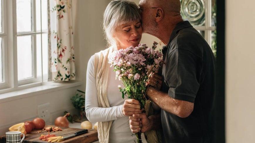 man kissing older woman in kitchen