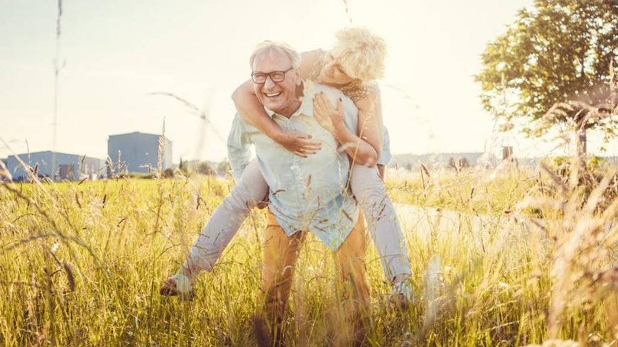 senior couple embracing in grasslands