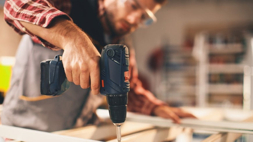 Tradesman working with a drill on wooden beam