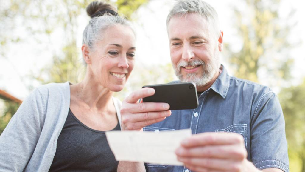mature couple scanning document with  phone