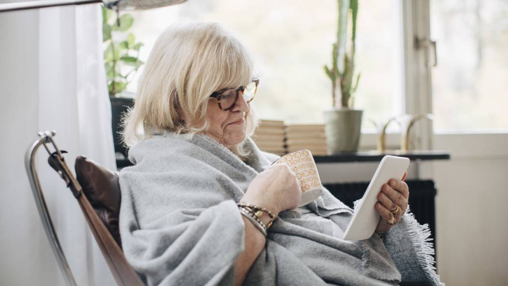senior woman using device to access social media