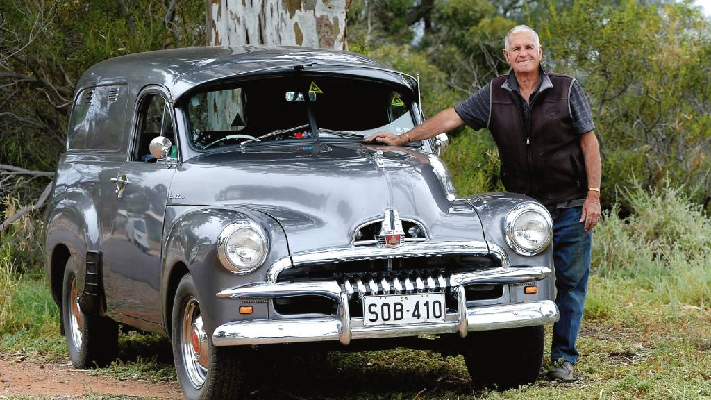 """Maurice """"Mozzie"""" McMahon poses with his restored 1954 FJ Holden panel van in Port Augusta, South Australia."""