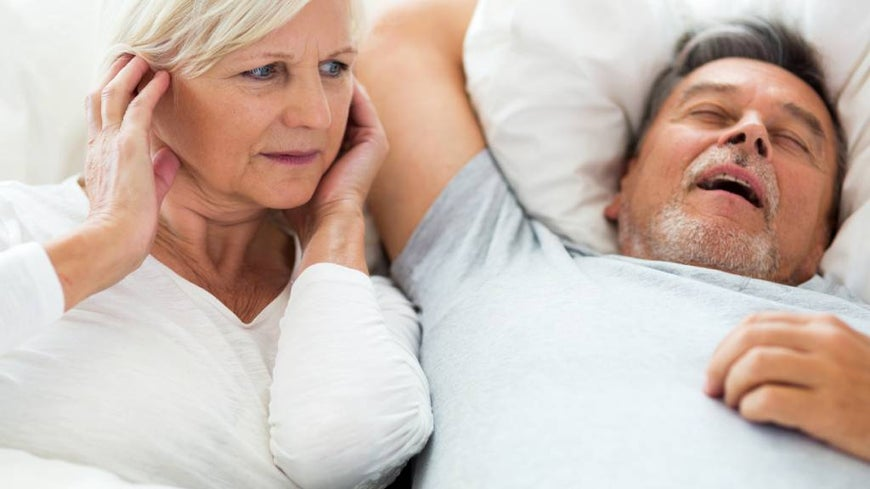 Senior man snoring and woman covering ears.