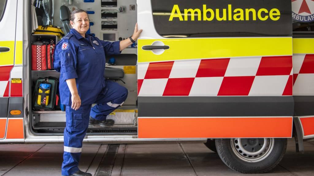 Paramedic Karen Martin stands in front of an ambulance