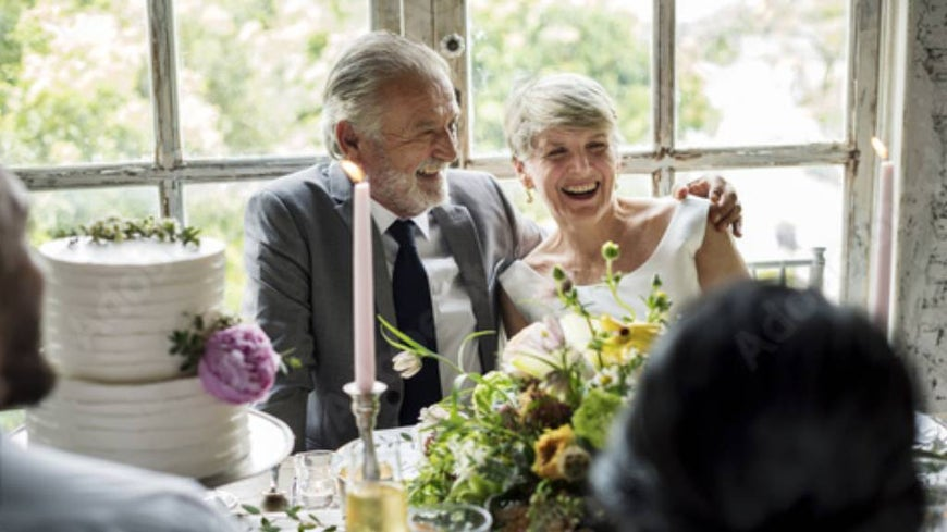 Senior couple at their wedding, surrounded by cake and decorations.