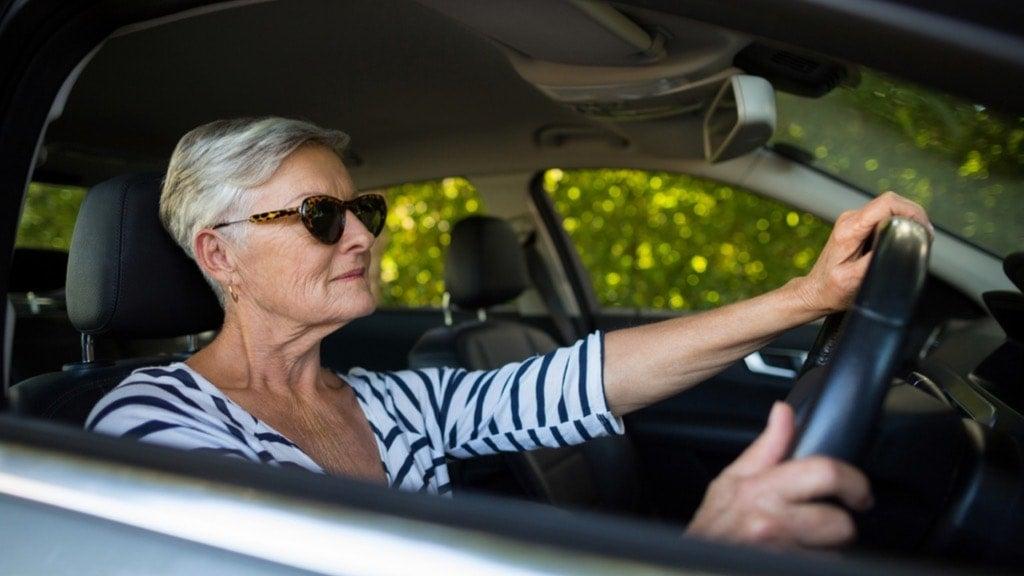 Senior woman driving new car