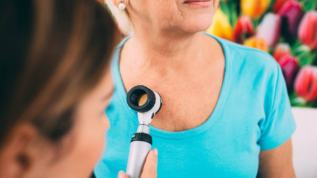 Seniors woman is examined by a dermatologist for skin cancer