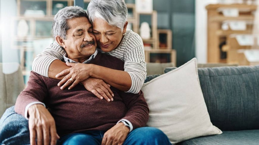 Older married couple embracing at home