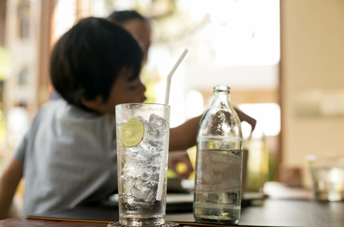 Boy drinking water with ice and lemon
