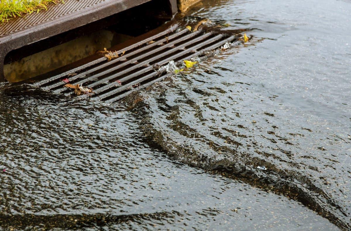 Heavy rain water going down a storm drain