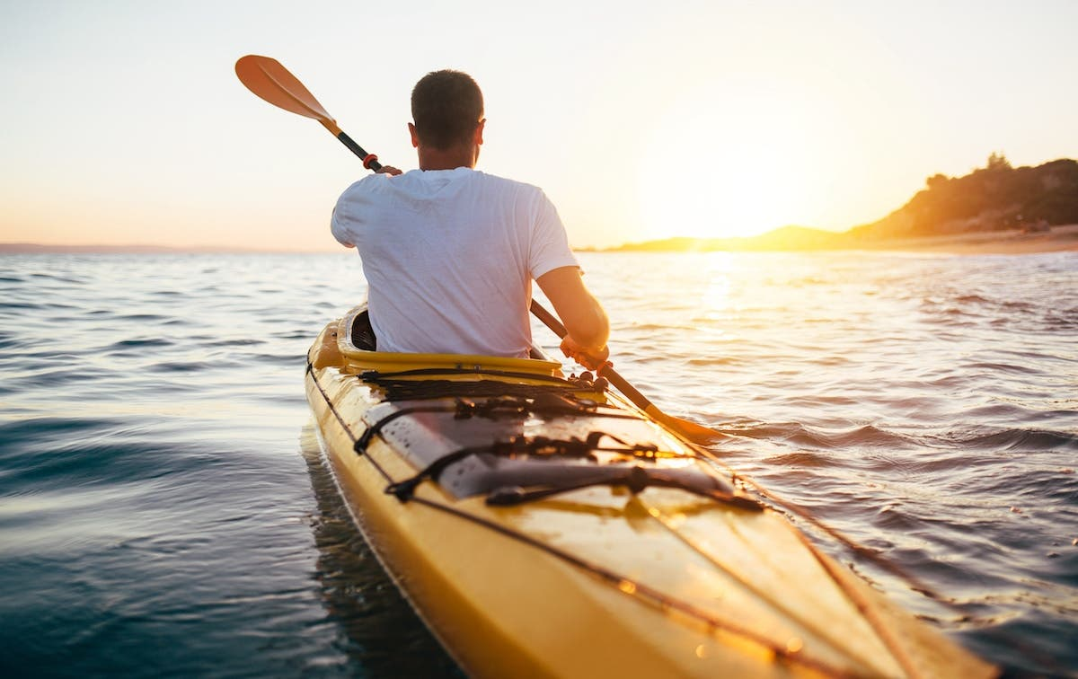 Guy on a canoe at sunrise, paddling in water