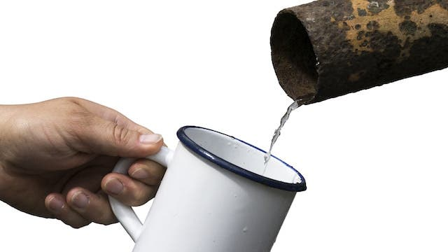 Water pouring into a tin cup, coming out of an old rusted pipe