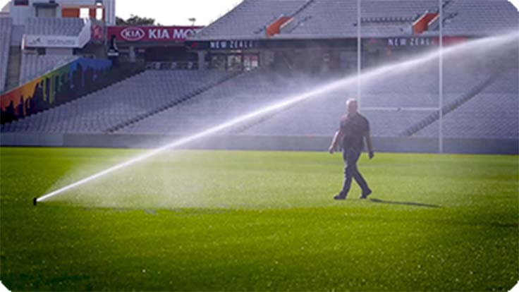 Eden Park Turf Manager walking towards sprinklers spraying water from new water bore