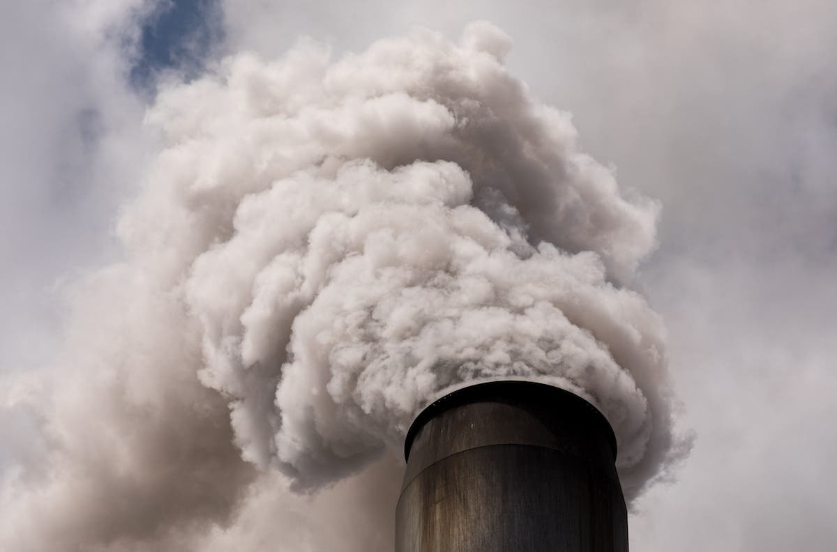 Thick smoke coming out of a industrial flue gas stack