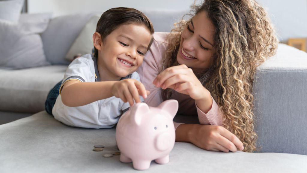 happy mother and son placing money in a piggy bank while laying on a couch