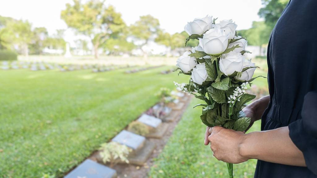 Mourning woman hold rose bouquet near stone gravestites