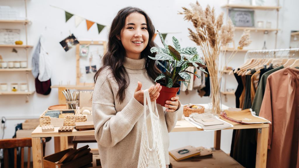 young woman smiling in ecological shop with eco-friendly products with a net bag and potted plant
