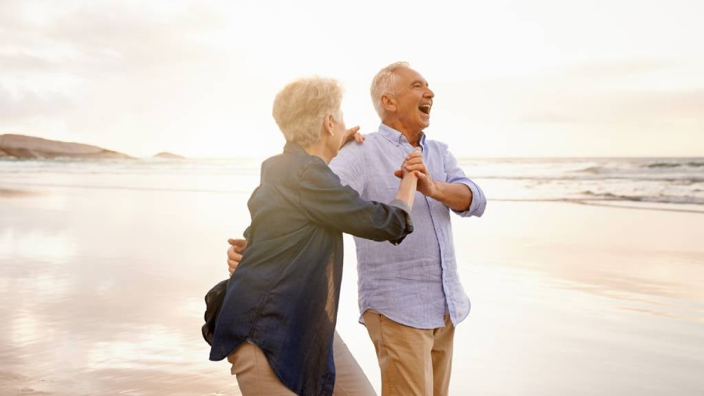 Senior couple happy and dancing on the beach.