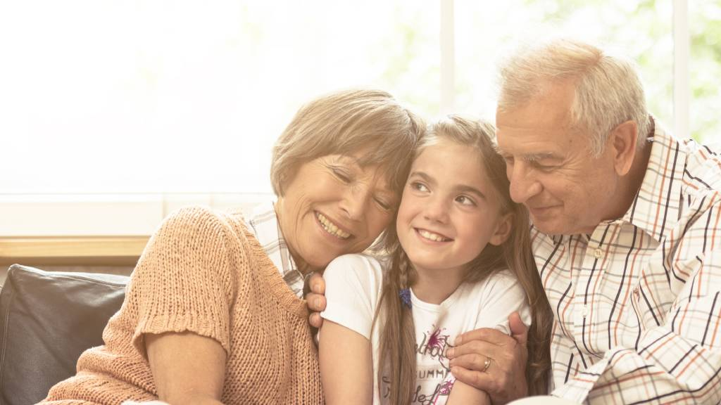 grandparents embracing young child