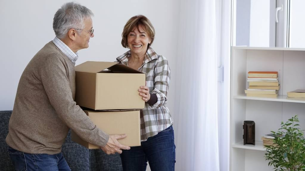 Senior couple carrying boxes while moving homes