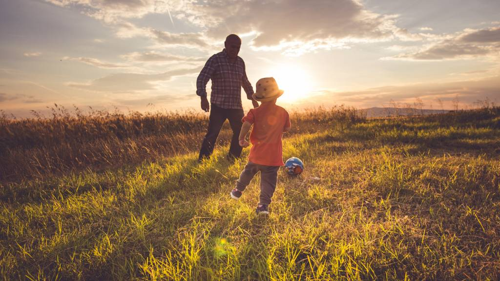 older man playing soccer outdoors with child