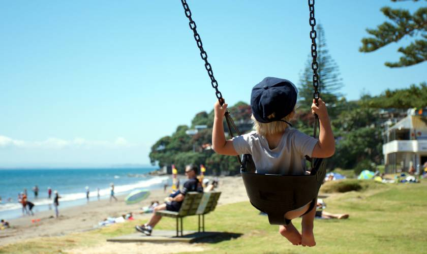 Child on a swing at a park in New Zealand's Auckland region