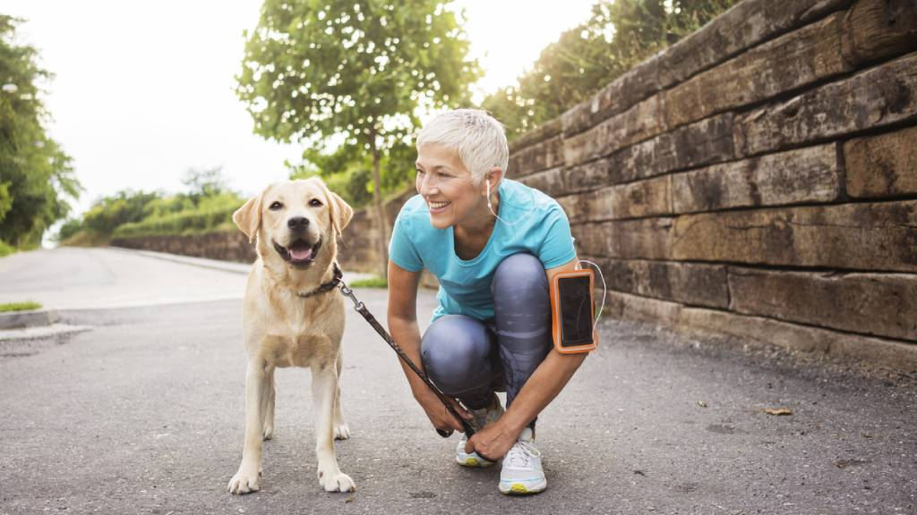 Retired woman exercising with golden retriever
