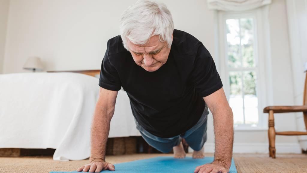 Senior man doing yoga at home