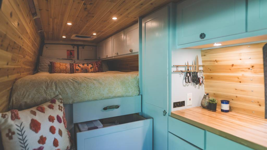 inside tiny home with tucked away bed and kitchen