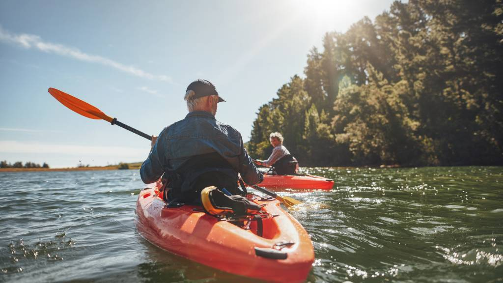 Older couple kayaking on a river with a red kayak
