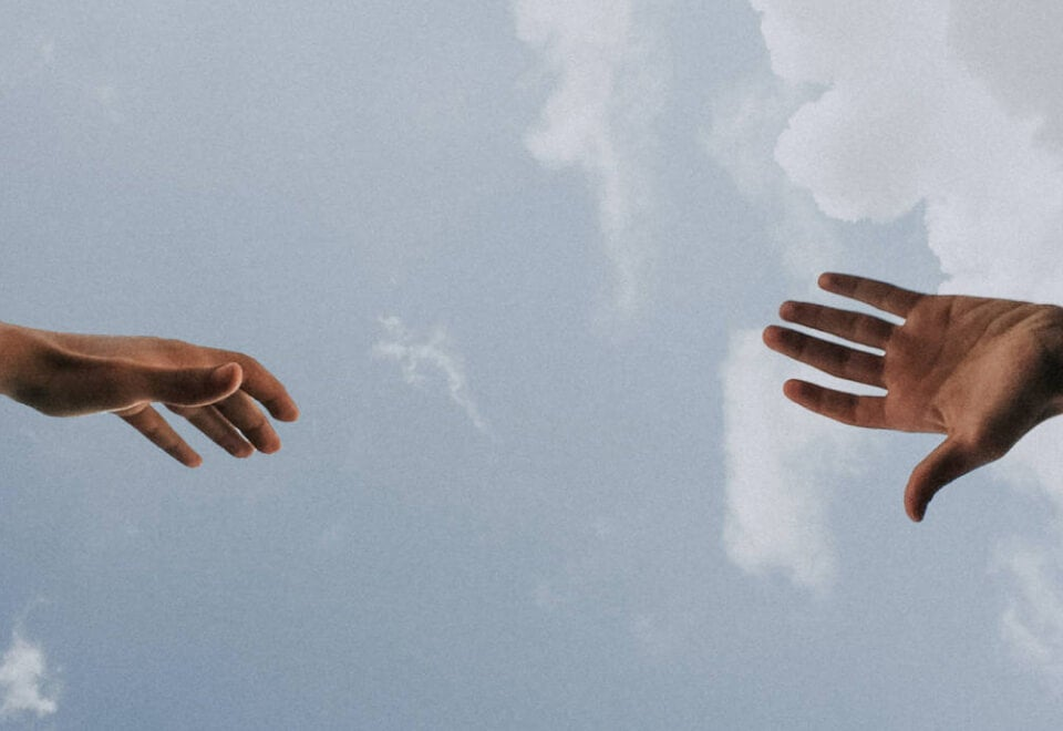 The Ethics Centre | two hands reaching out to each other with a cloudy sky in the background | Devotion