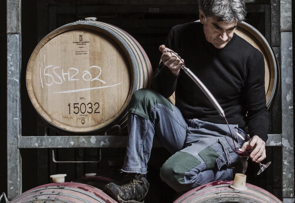 Wine Australia | man kneeling on a wine barrel pouring wine into a glass | Devotion